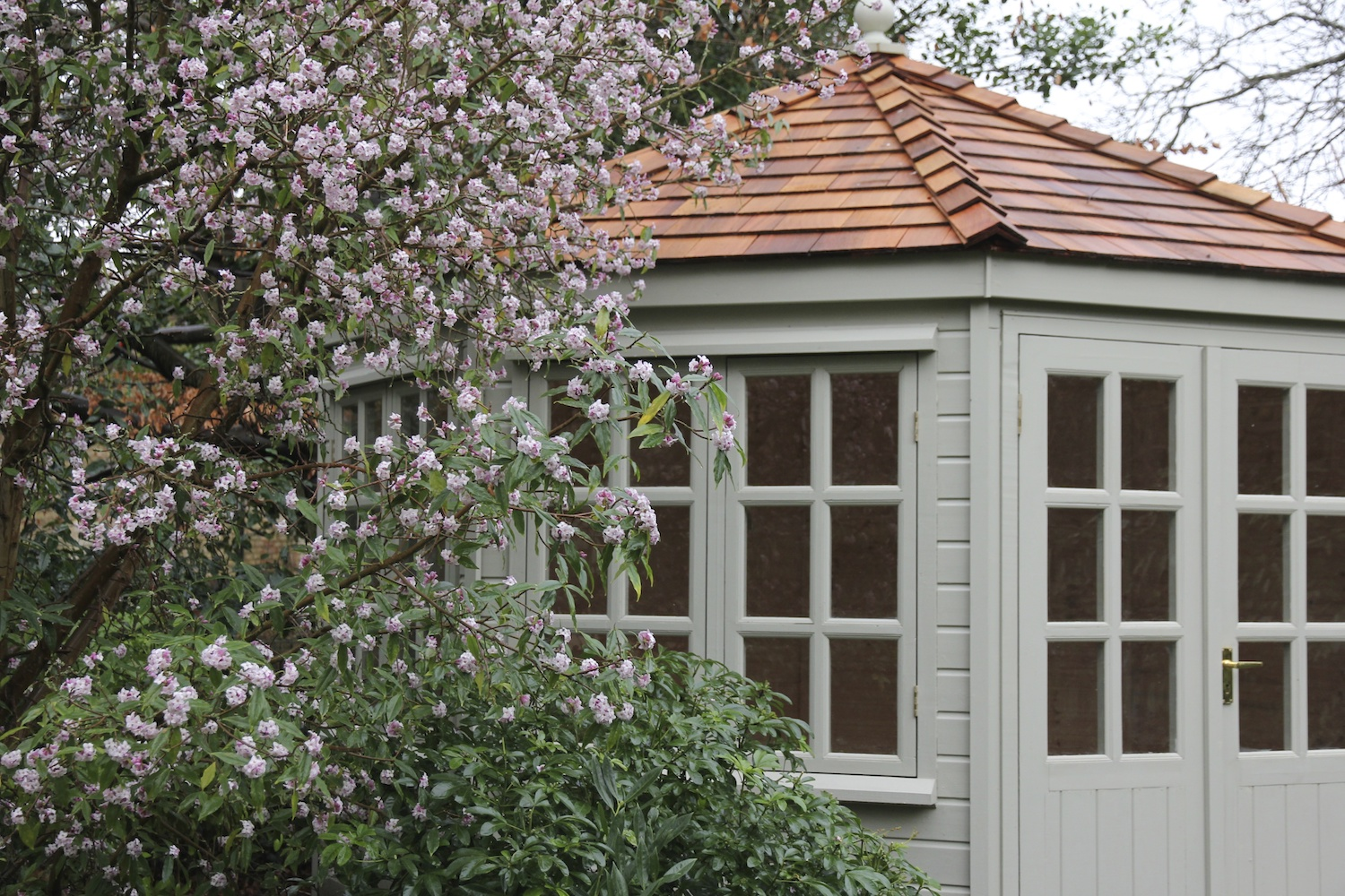 a summerhouse with cedar shingle roof and spring blossom
